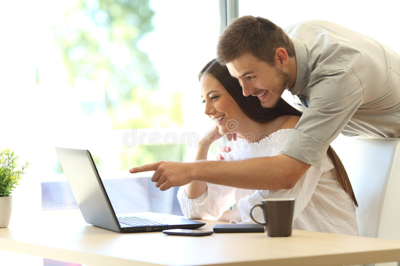 Couple searching online in a laptop at home royalty free stock image