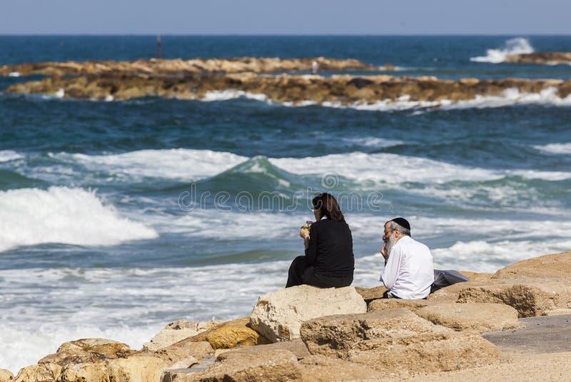 Couple at the seashore enjoys the view. Tel Aviv, Israel stock image