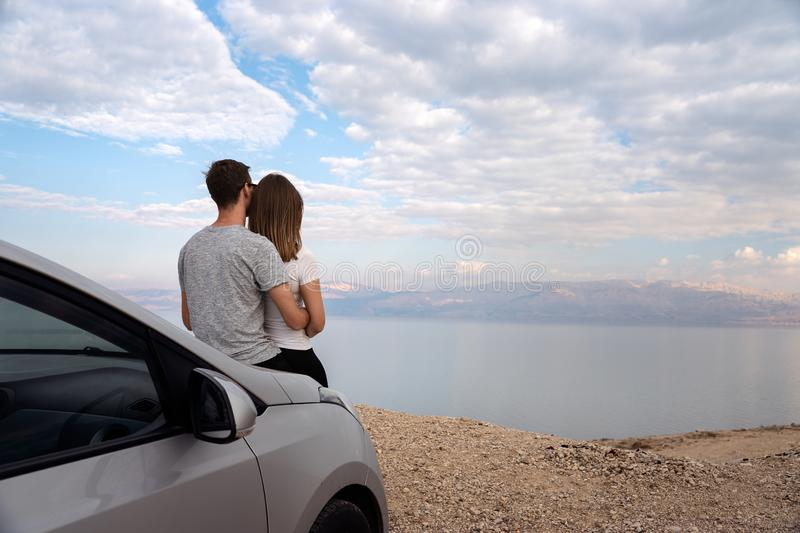 Couple seated on the engine hood of a rented car on a road trip in israel. Couple seated on the engine hood of a rented car. Dead sea as background royalty free stock images