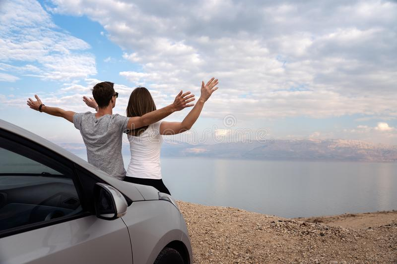Couple seated on the engine hood of a rented car on a road trip in israel. Couple seated on the engine hood of a rented car. Dead sea as background royalty free stock photo