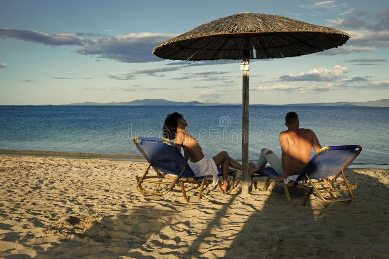 Couple secrets fantasy. Couple in love at sea resort sits on loungers under umbrella on sand beach. Couple on vacation royalty free stock images
