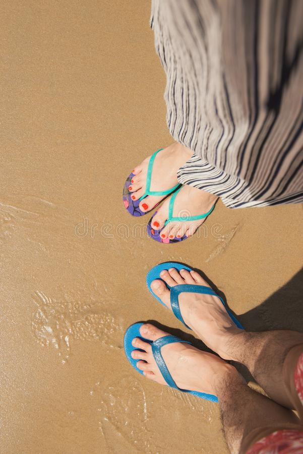 Couple selfie of feet in sandals shoes on beach sand background stock photography