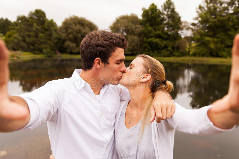 Couple selfie kissing stock images