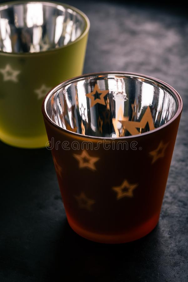 Couple of semi transparent cups with candle inside. Vertical photo of two color semi-transparent cups with shiny surface from inside. Transparent stars are on stock photography