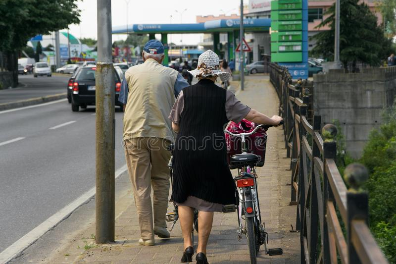 Couple of senior adult walk with bicycles royalty free stock photos