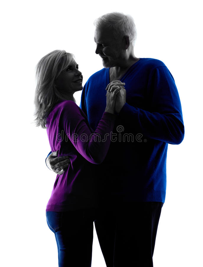Couple senior lovers dancing silhouette. One caucasian couple senior lovers dancing silhouette in silhouette studio isolated on white background stock photography