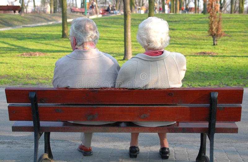 A couple of seniors. Sitting on the park bench stock images