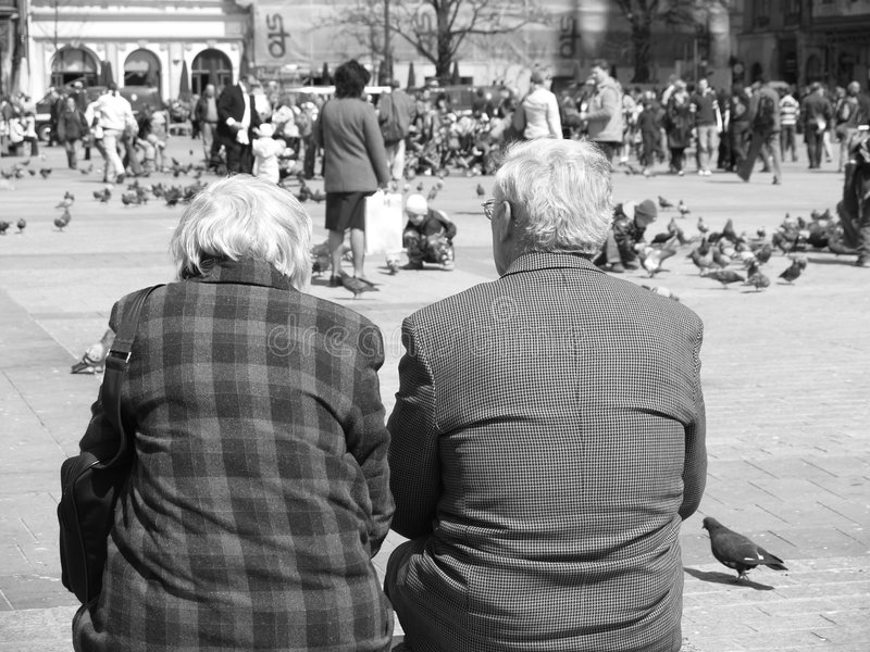 A Couple Of Seniors. Couple sitting on a bench taking in the view stock image