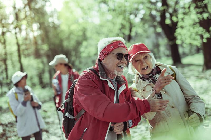 Couple of seniors exploring forest fauna together. Pointing at the animal. The couple of seniors exploring forest fauna together stock image