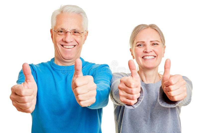 Couple of seniors holding their thumbs up royalty free stock photography
