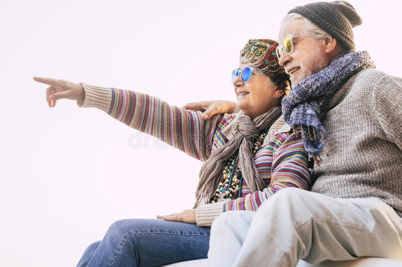 Couple of seniors hugged together with winter clothes smiling and showing something - happy mature people together in outdoor. Leisure activity royalty free stock photo