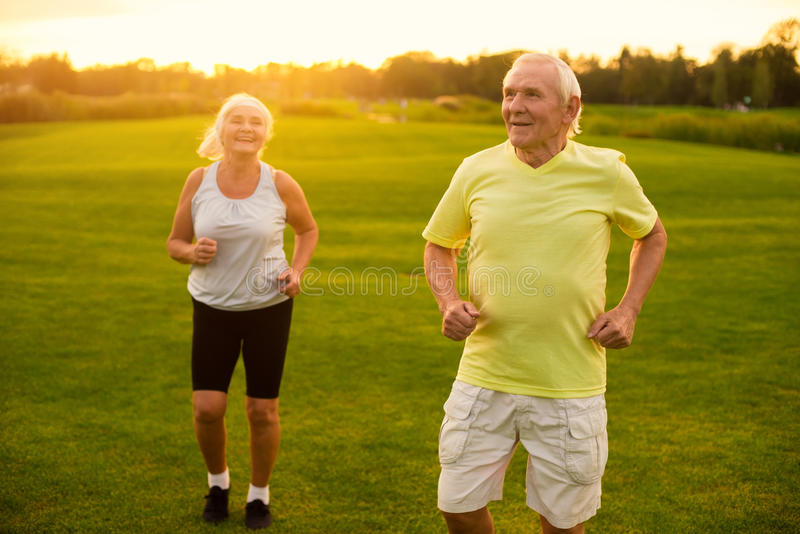 Couple of seniors jogging. Two people on nature background. Pensioners training in open air. Athletes don't get old royalty free stock photos