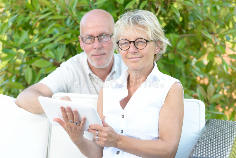 A couple of seniors look at a digital tablet. Outside stock images