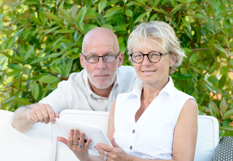 A couple of seniors looking at digital tablet. Outside royalty free stock images