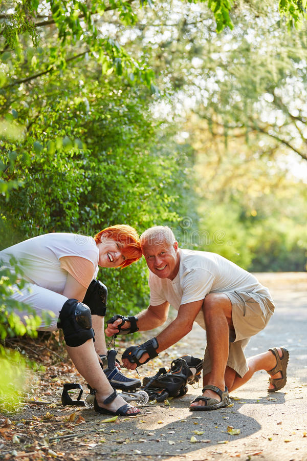 Couple of seniors looking forward to inlineskating. In the park stock photos
