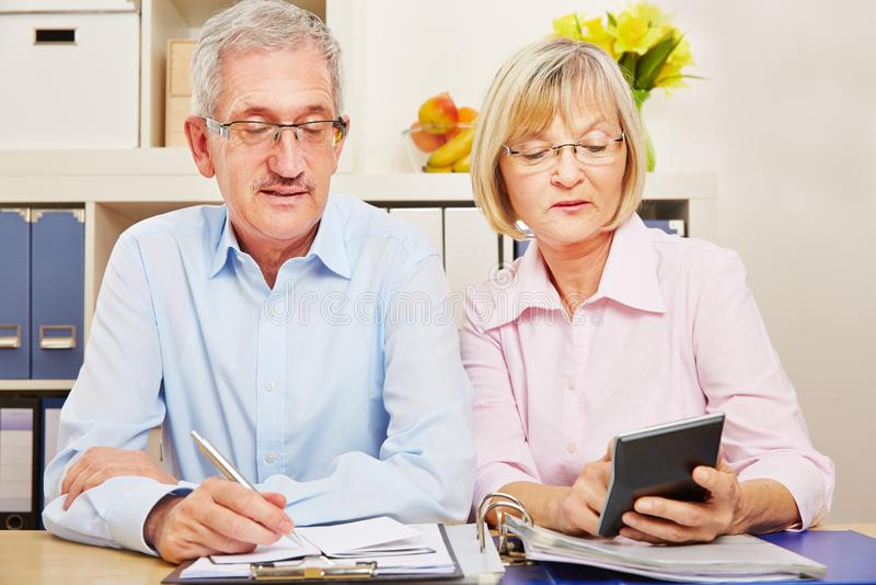 Couple of seniors makes tax return stock photos