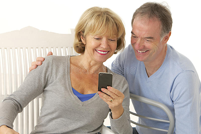 Couple of seniors with mobile phone - happy and smiling. Playing with mobile phone royalty free stock image