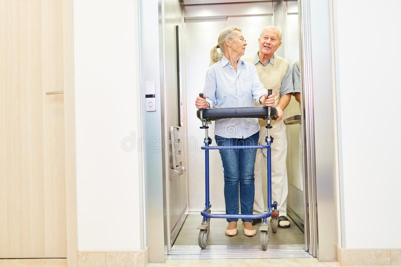 Couple of seniors with rollator in the lift royalty free stock photography