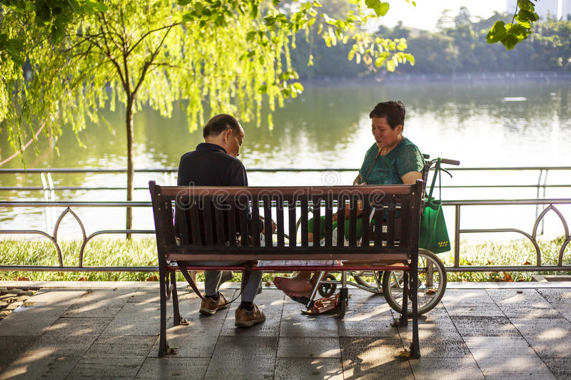 A couple of seniors. Sitting on the park bench royalty free stock images