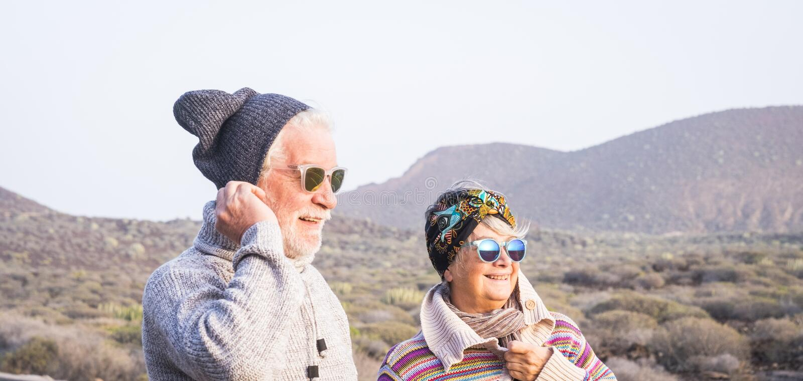 Couple of seniors together in outdoor leisure activity. Couple of seniors together looking at the horizon with the mountain in background. travelers at winter stock images