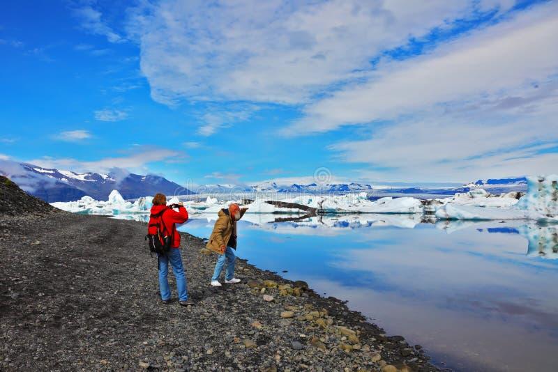 Couple of seniors tourists photographs. ICE LAGOON, ICELAND - JULY 10, 2014: Couple of seniors tourists walking and photographs on the banks of the lagoon Ice stock photo
