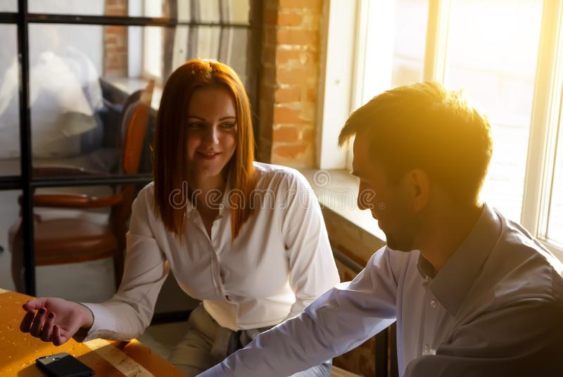 Couple of serious business partners working in modern office. Two coworkers discussing new project while working on royalty free stock photo