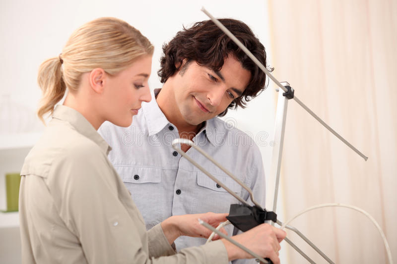 Couple setting up an antenna stock images