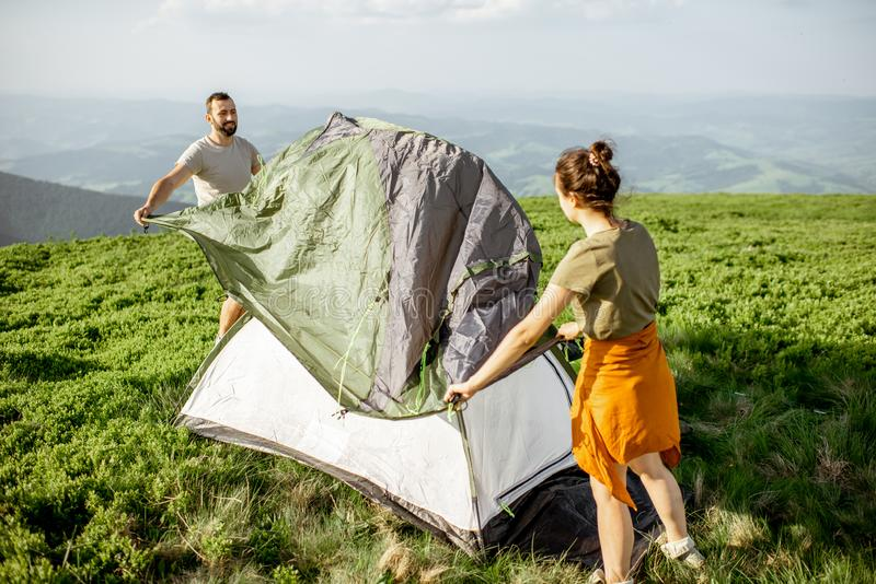 Couple setting up the tent in the mountains royalty free stock photos
