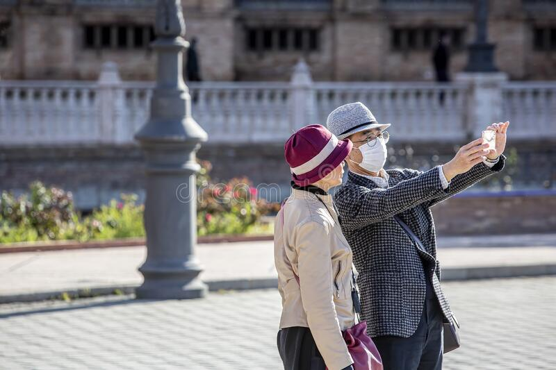 Couple in Seviille Spain taking selfie while one wears mask to prevent the spread of coronavirus. SEVILLE, SPAIN  - March 7: Unidentified couple with man wearing royalty free stock photo