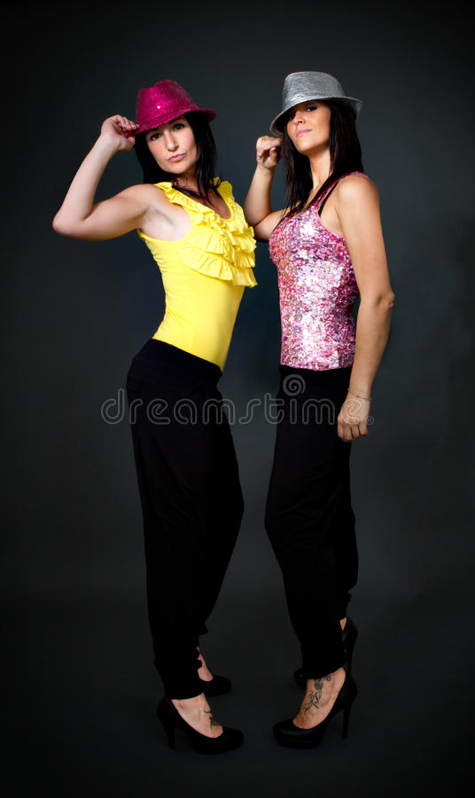 Couple of woman ready for dance and disco. Couple of women ready for dance and disco, gray background royalty free stock images