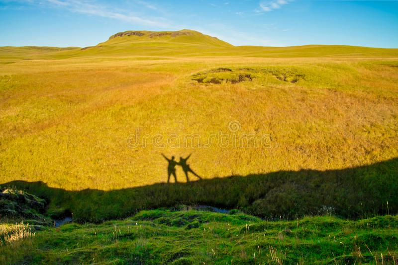 A Couple shadow on grass hill royalty free stock image