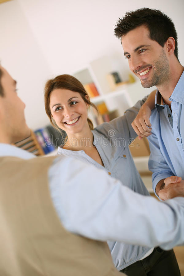 Couple shaking hand to architect. Cheerful couple shaking hand to salesman royalty free stock photo