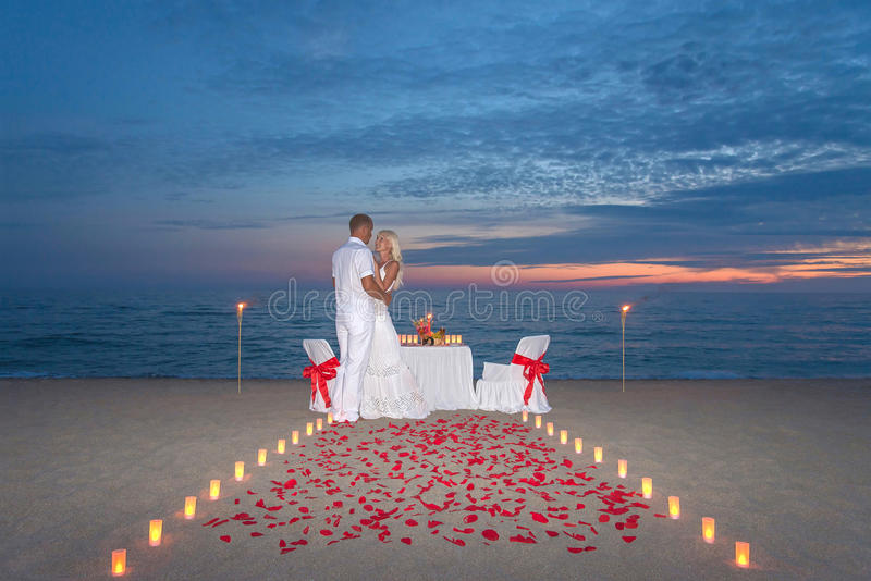 Couple share a romantic dinner with candles. Young couple share a romantic dinner with candles, torches and way or rose petals at sea sandy beach against sunset royalty free stock image