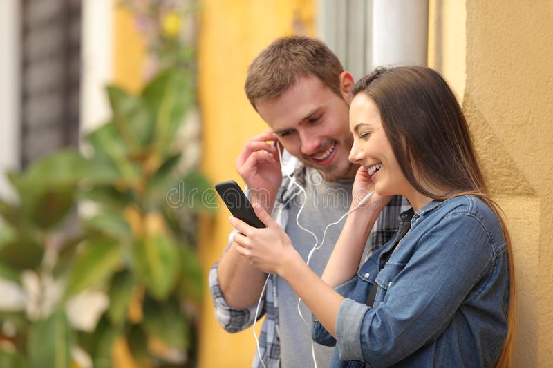 Couple sharing earphones to watch media on phone royalty free stock image