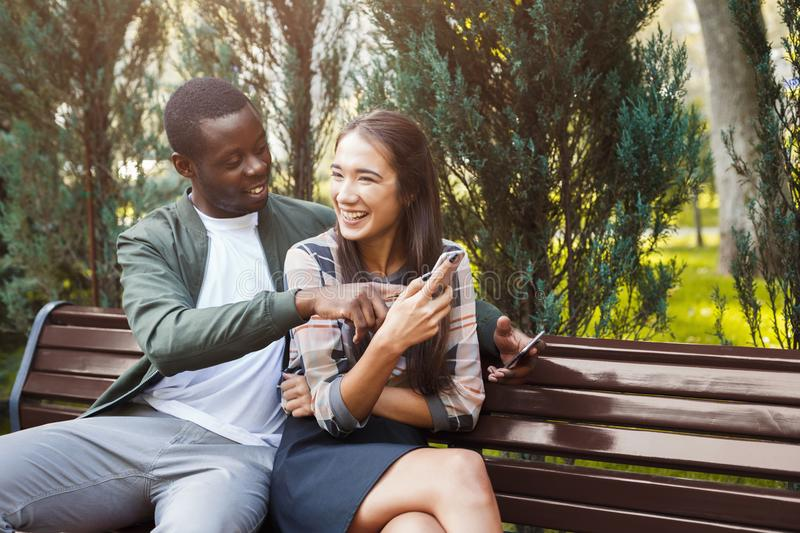 Couple sharing media in smartphone copy space. Couple sharing media in smart phone sitting on bench in park,having romantic date. Modern lifestyle, communication stock photo