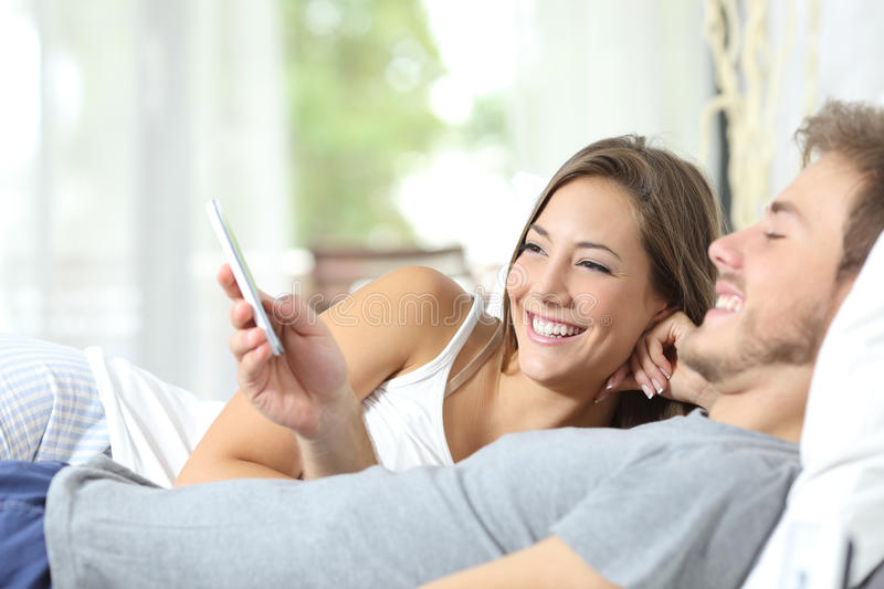 Couple sharing a smart phone on the bed. Happy couple sharing a smart phone watching media content on the bed