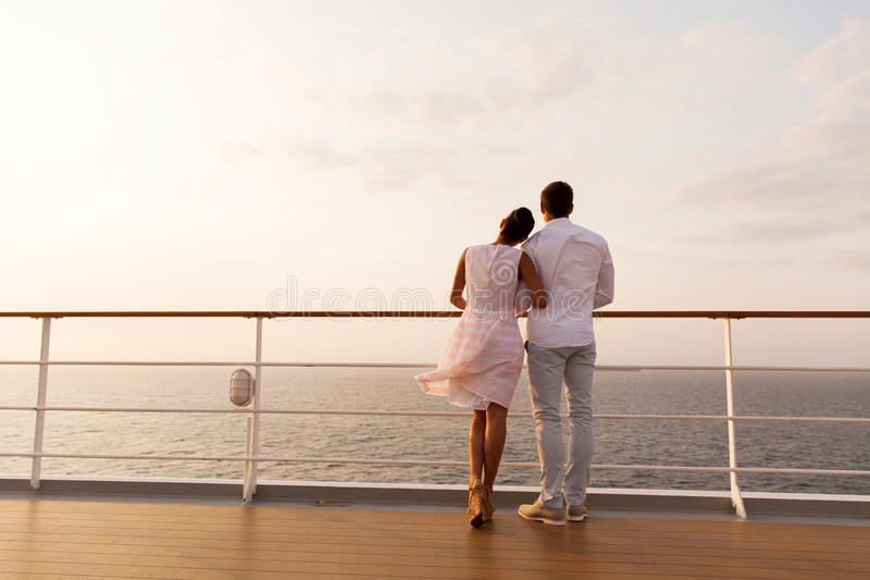Couple ship deck. Rear view of young couple standing on ship deck during sunset royalty free stock images