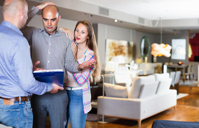 Couple shocked from looking through price-list. Couple shocked and astonished from looking through price-list for furniture royalty free stock photos