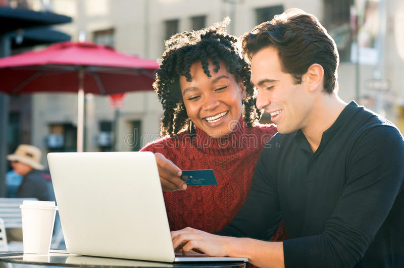 Couple shooping online with credit card. Beautiful young loving couple shopping online together while women holding credit card and smiling. Portrait of happy stock photo