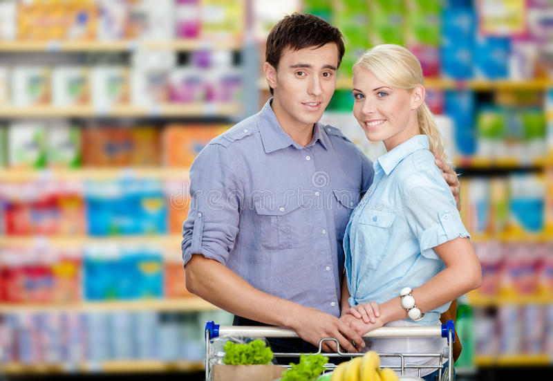 Couple in the shop with cart full of food. Half-length portrait of couple in the shop with cart full of food. Concept of consumerism and healthy food royalty free stock image