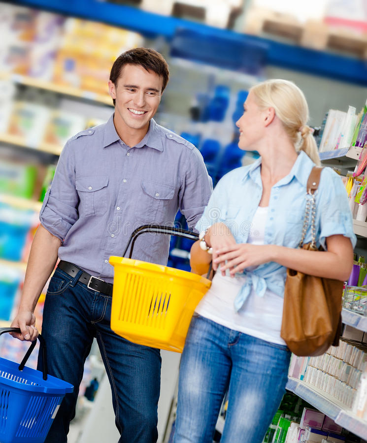 Couple in the shop with carts. Happy couple handing carts in the shop. Concept of consumerism and retail royalty free stock image