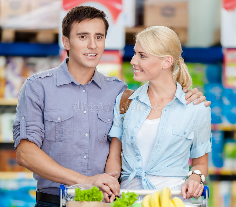 Couple in the shopping center with cart full of food. Half-length portrait of couple in the shopping mall with cart full of food. Concept of consumerism and royalty free stock image
