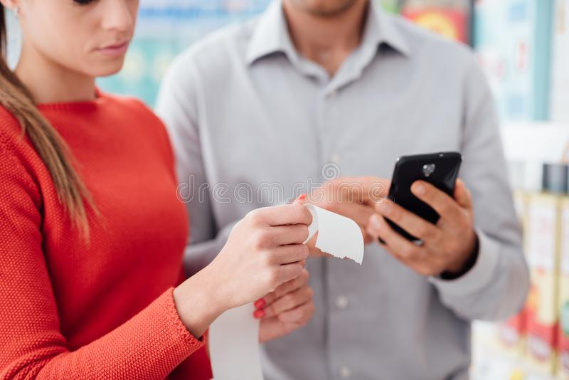 Couple shopping and checking a receipt. Couple doing grocery shopping at the supermarket they are checking a long receipt and using apps on the phone royalty free stock photo