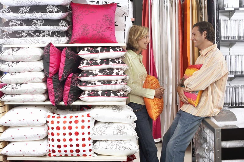 Couple shopping for cushions in department store, standing face to face, smiling, side view stock photo