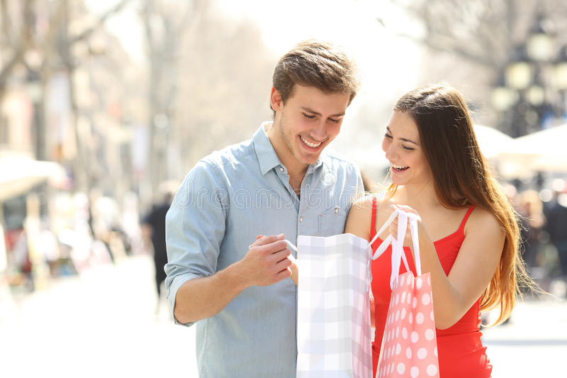Couple shopping and holding bags in the street royalty free stock photo
