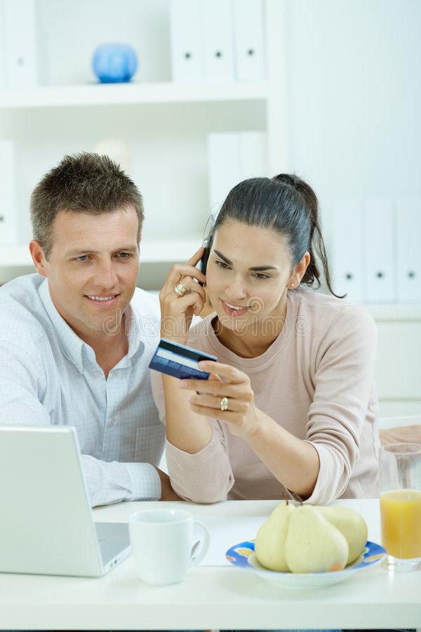 Couple shopping on internet. Young couple sitting at desk shopping on internet from home. Calling phone, using laptopcomputer and paying with credit card royalty free stock photos