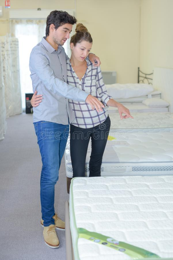 Couple shopping for mattress. Bed stock photos