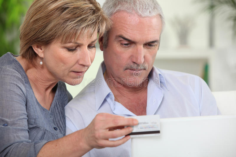 Couple shopping online. Older couple shopping online for goods stock image