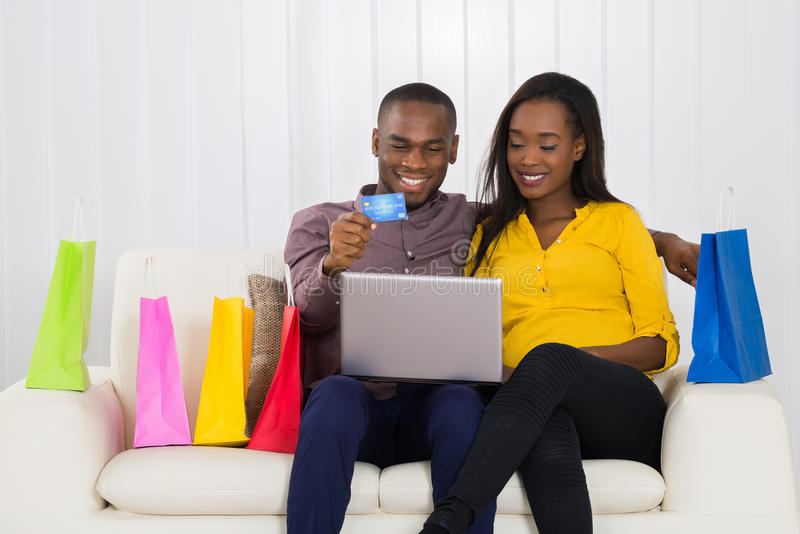 Couple Shopping Online With Credit Card. Young Couple Sitting On Sofa Shopping Online With Credit Card stock photos