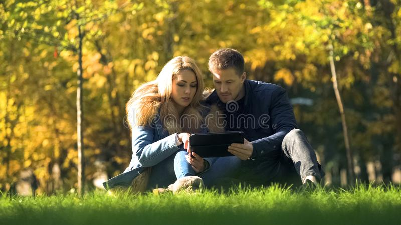 Couple shopping online, using tablet at autumn park, buying warm clothes in net. Stock photo stock image